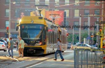 Light rail yang juga sedang berjalan tetapi dua orang penyeberang jalan santai menyeberang jalan.