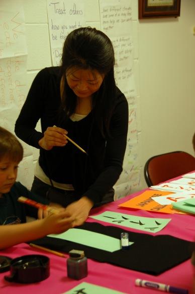 Perempuan Jepang yang sedang mengajarkan kaligrafi ke salah satu anak SD